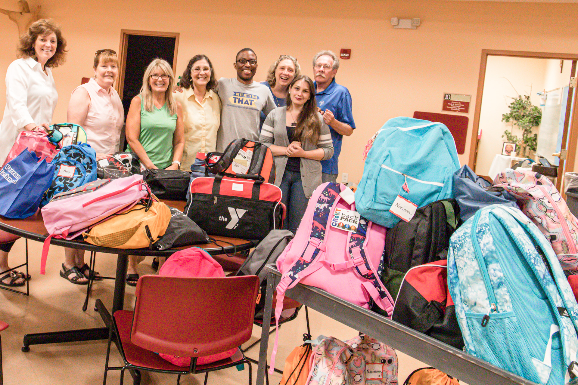 Volunteers from McC with the overwhelming donation of backpacks and school supplies.