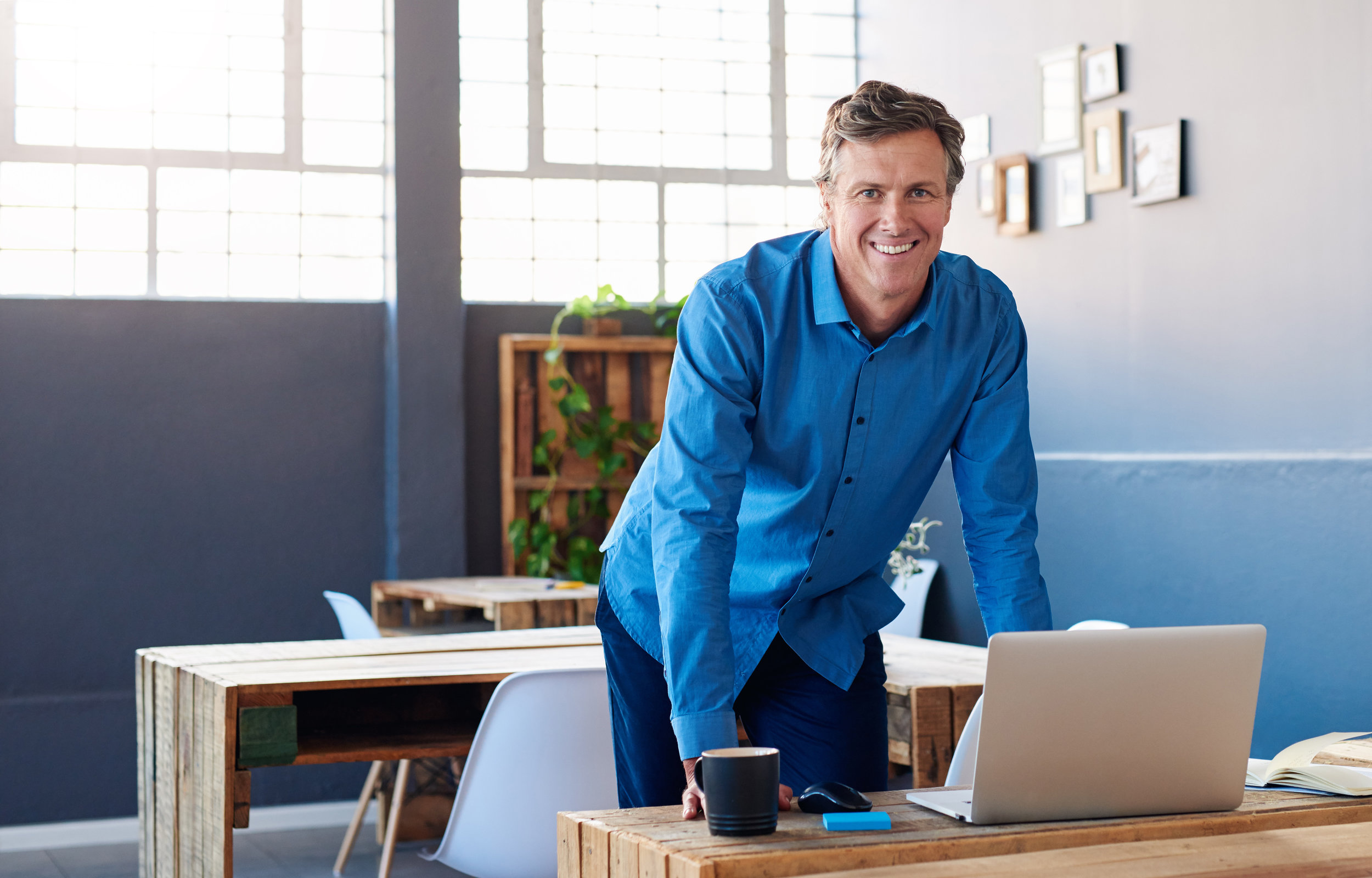 Smiling mature businessman leaning on his desk in an office