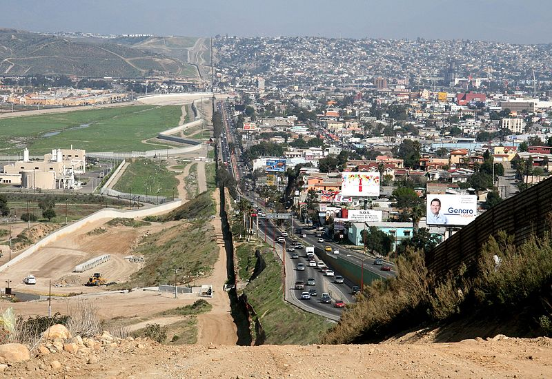 The border crossing between the U.S. (left) and Tijuana, Mexico (right), via Wikimedia. * The main caravan has made it to the Tijuana border crossing , where migrants await further legal action in order to enter the U.S.