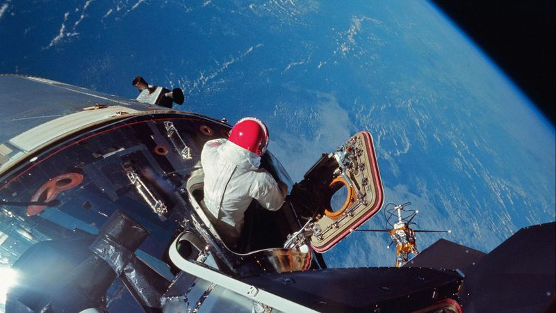Apollo 9 CM pilot Dave Scott emerges from the hatch, testing some of the spacesuit systems that will be used for lunar operations. The photo was taken from the hatch of the docked LM by Rusty Schweickart in March 1969. (NASA)