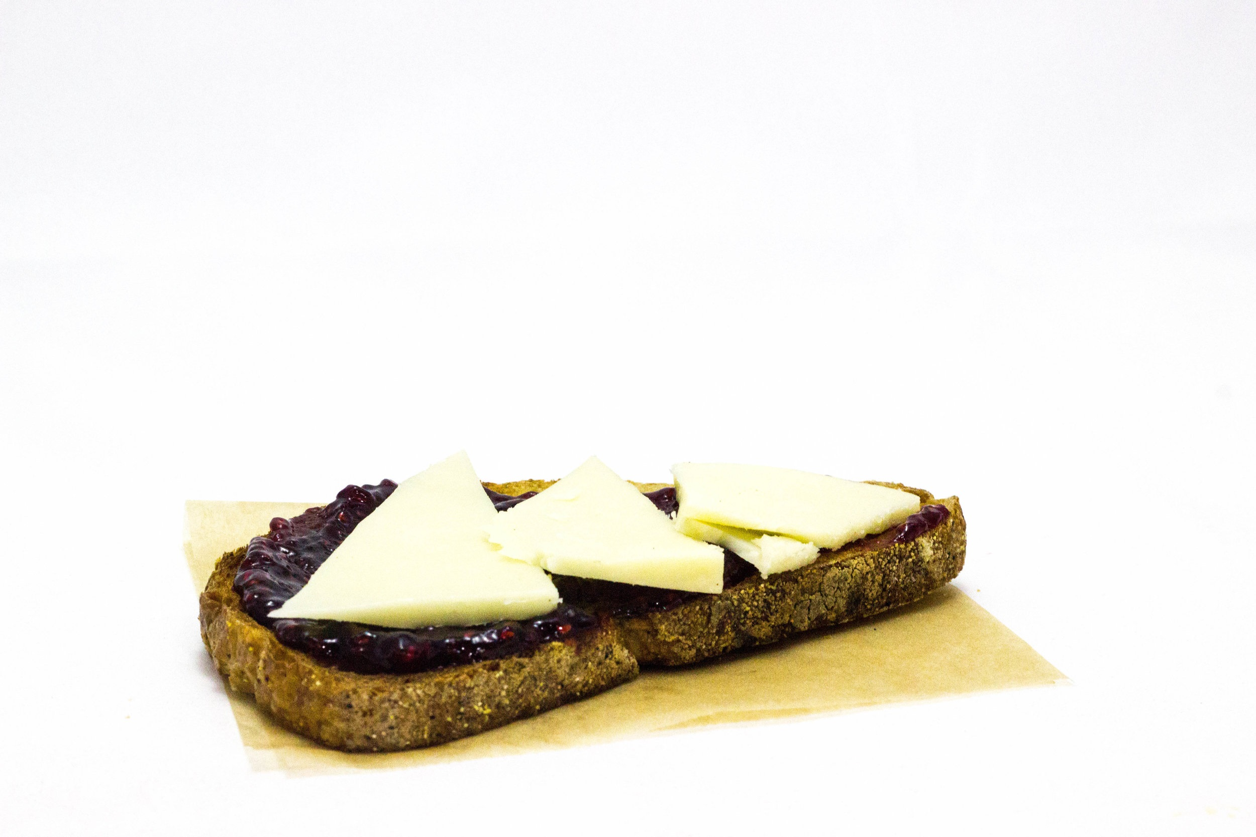 Cheddar + Jam Toast - Soda bread slice topped with raw white cheddar and your choice of strawberry or raspberry jam