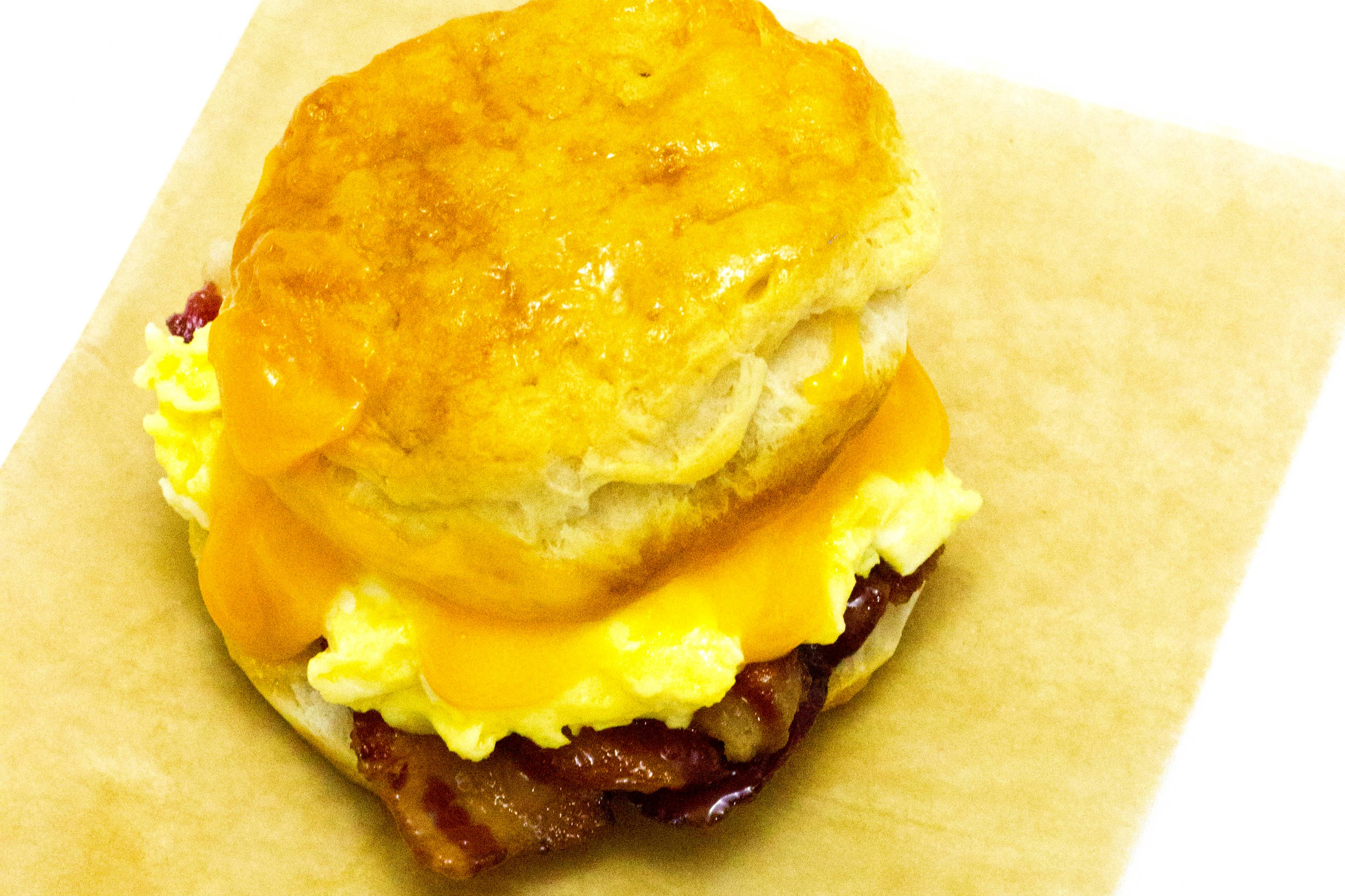 Biscuit Sandwich - Homemade biscuit topped with bacon, cheddar, herb seasoned eggs and homemade chipotle aioli or jalapeno aioli