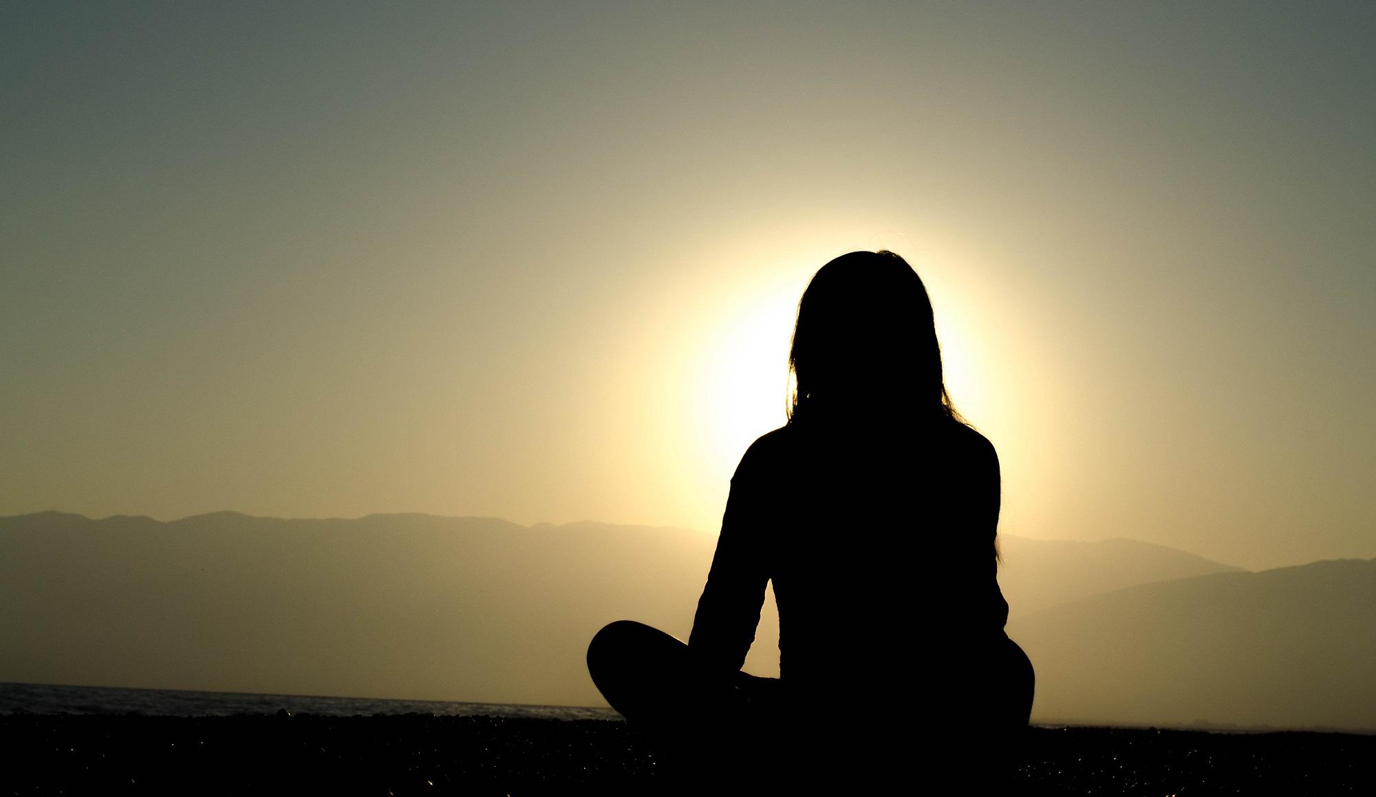 Mulher a meditar virada para o pôr do Sol