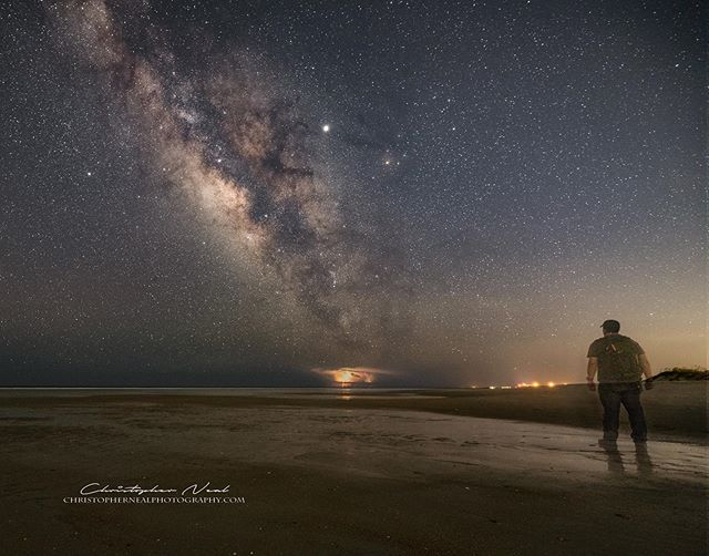 Far Away - Fellow astro-shooter Lou Vega watching thunderstorms flashing on the horizon far away to the south off Charleston. It was nice to have some company on the beach for a change. ⁠⠀ -⁠⠀ -⁠⠀ -⁠⠀ #milkyway #pawleysisland #astrophotography #stars #milkywaychasers #southcarolina #natgeospace #sigma #scphotographer #nikon #night #nightimages #thunderstorm #nikonartists #benrousa #YourShotPhotographer #NikonD750 #NikonUSA #discover_carolinas #photopills #nightscaper #longexposure #longexpohunter #milkywaygalaxy #newmilkyway #lonelyplanet #thegreatmilkywaychase #lightning #astrophotographer #nightskyphotography⁠⠀
