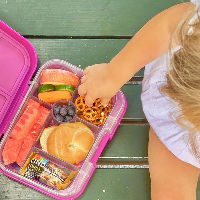 This is how we roll in the summer ☀️—with a lunchbox packed with allllll the snacks. What are your camp/park/pool go-to's? I like the fill the kids' @yumboxlunch boxes with snacks that pass as lunch: plenty of fruit and veggies, mini @thomasbreakfast 🥯, pretzels, and @kindsnacks minis.  Eating a a healthy lunch means that mom will always say yes to the ice cream truck in the afternoon. 🍦