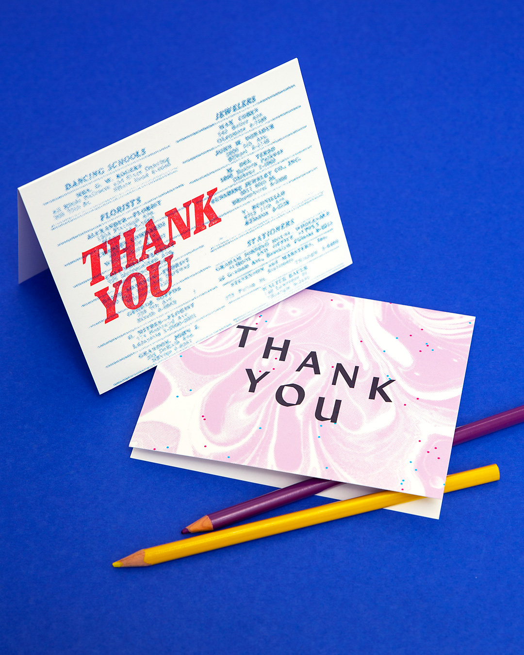 Two colorful Ephemora Thank You Cards sit on a blue background with colored pencils arranged nearby.