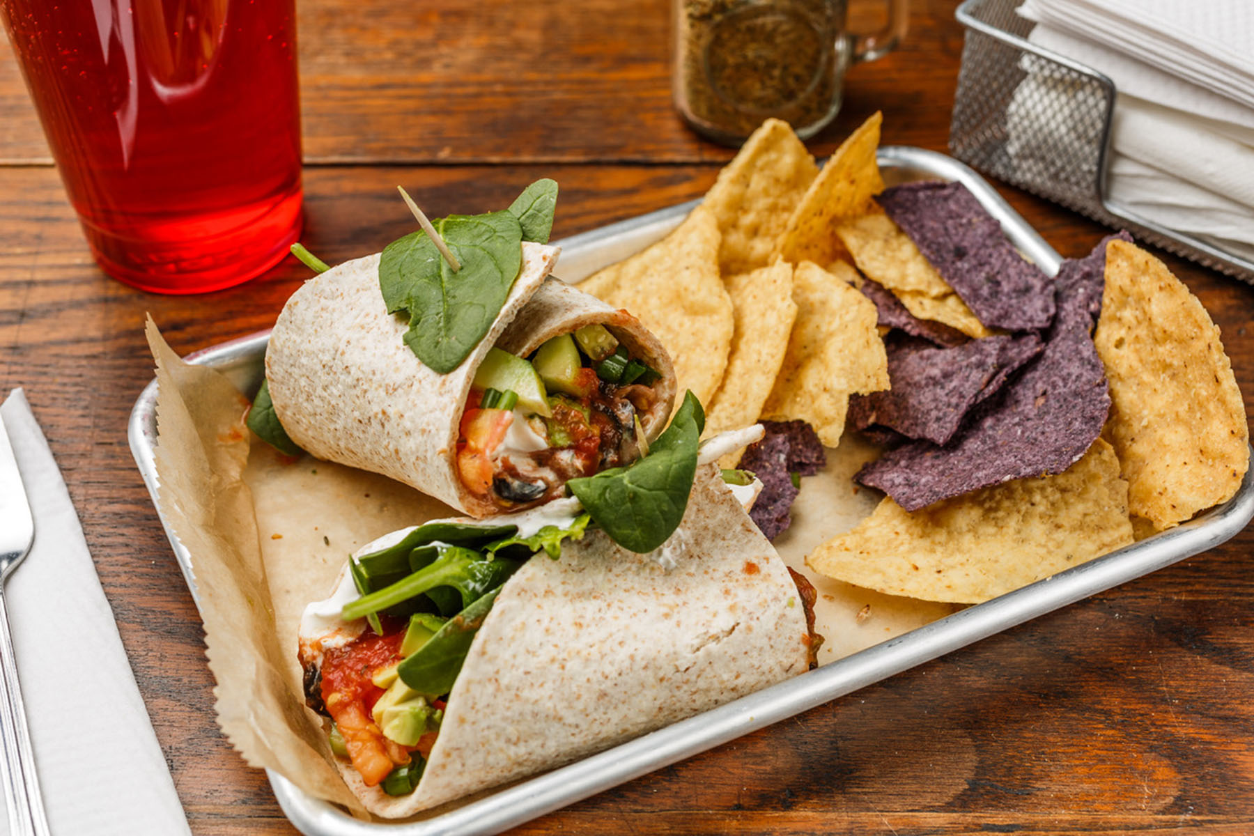 Veggie Burrito  Organic whole wheat tortilla, avocado, tomato, green onions, jalapeño, cucumber, black olives, sour cream, salsa, and spinach or sprouts. Served with organic tortilla chips.   $6.49