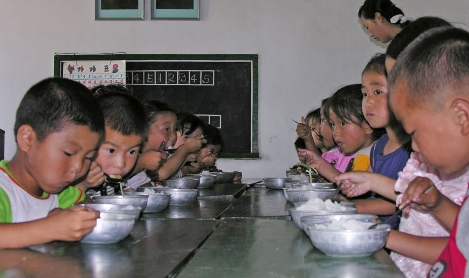 FILE - North Korean children eat lunch at a government-run kindergarten in Taedong county in south Pyongan province, July 18, 2005