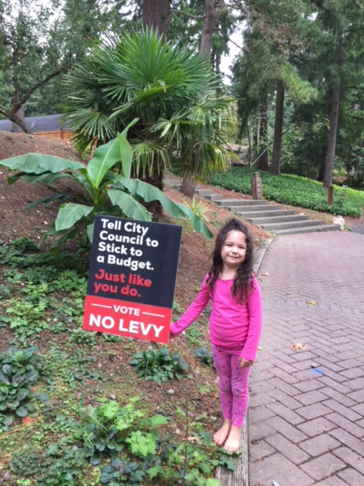 Colette with budget sign.PNG