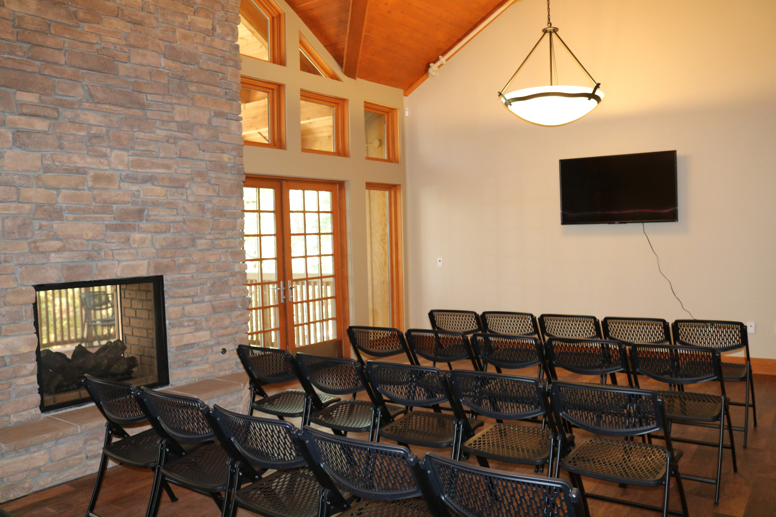 Lodge Meeting Rooms - There is a meeting room identical to the one pictured in each of the three Lodges. Each Meeting Room is available to the guests staying in their perspective Lodge. The room is equipped with an indoor/outdoor fireplace, along with a smart TV and HDMI cable for presentations.