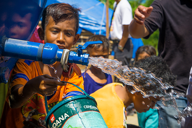A boy gets water from a CWS truck. He is one of more than 13,000 people who CWS delivers water to each day.