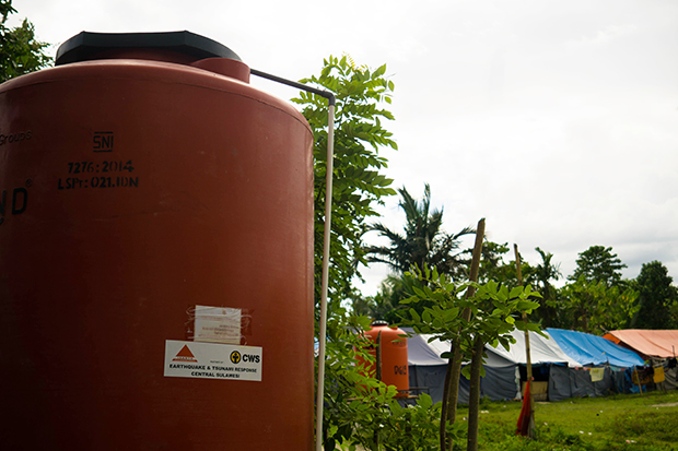 A CWS-provided water tank. Behind it are tents, where survivors who lost their homes are living temporarily.