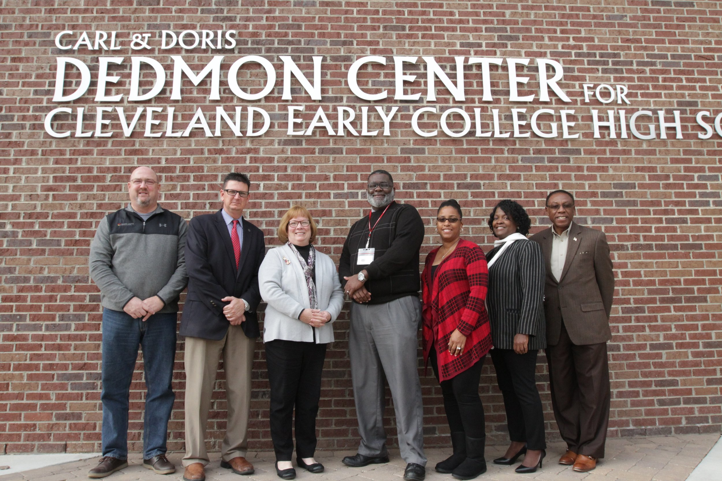 CCS school board members, superintendent, assistant superintendent standing outside Cleveland Early College High with Regional Principal of the Year Titus Hopper.