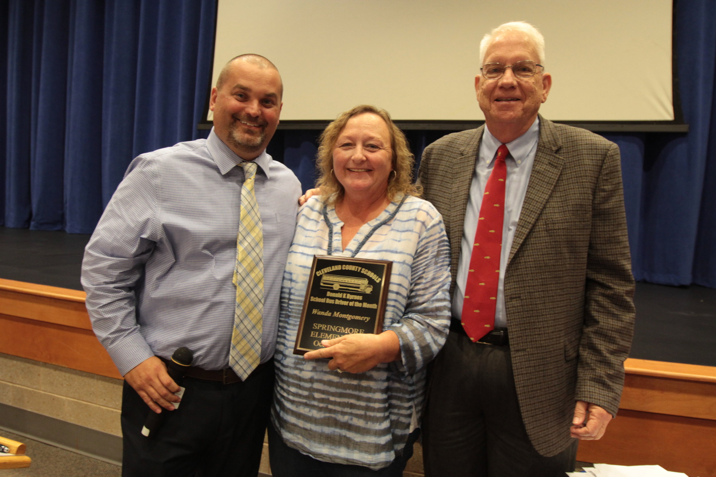 Pictured left-to-right: Transportation Director David Pless, 2019 Bus Driver of the Year Wanda Montgomery, and Retired Transportation Director Donald K. Byrnes