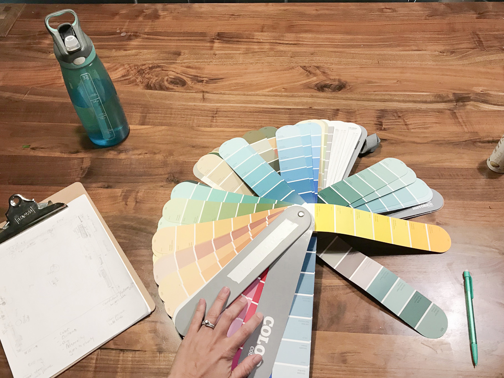 A paint fan deck and clipboard with a room design on a desk.