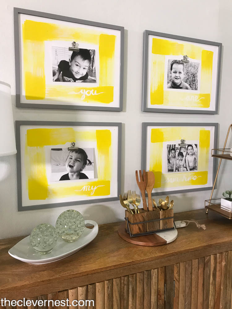 Four yellow picture frames with black and white pictures clipped to them, hanging above a buffet