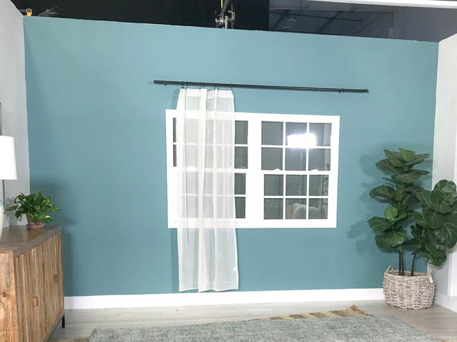 White curtains hung over a window with a blue wall for the makeover.