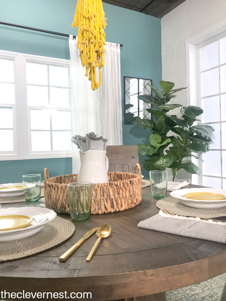 a round wooden table set with white dishes and a basket centerpiece for a coastal look