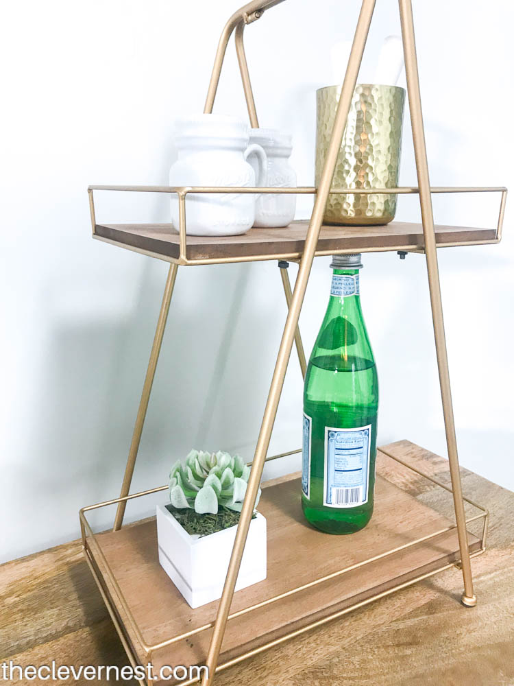 gold beverage tray styled with glasses and plants sitting on a wooden buffet
