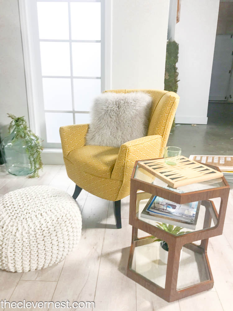 yellow side chair and white pouf next to a side table holding boardgames