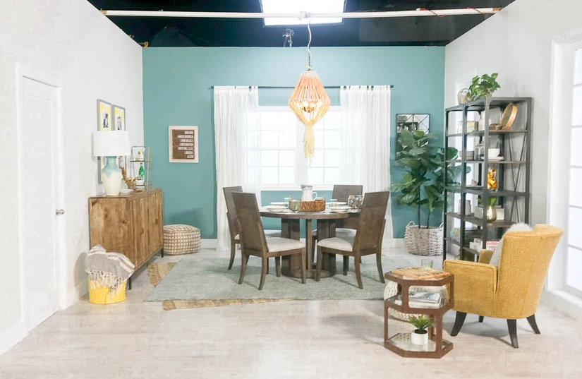 A coastal dining room decorated in teal and yellow with a bookcase and side chair