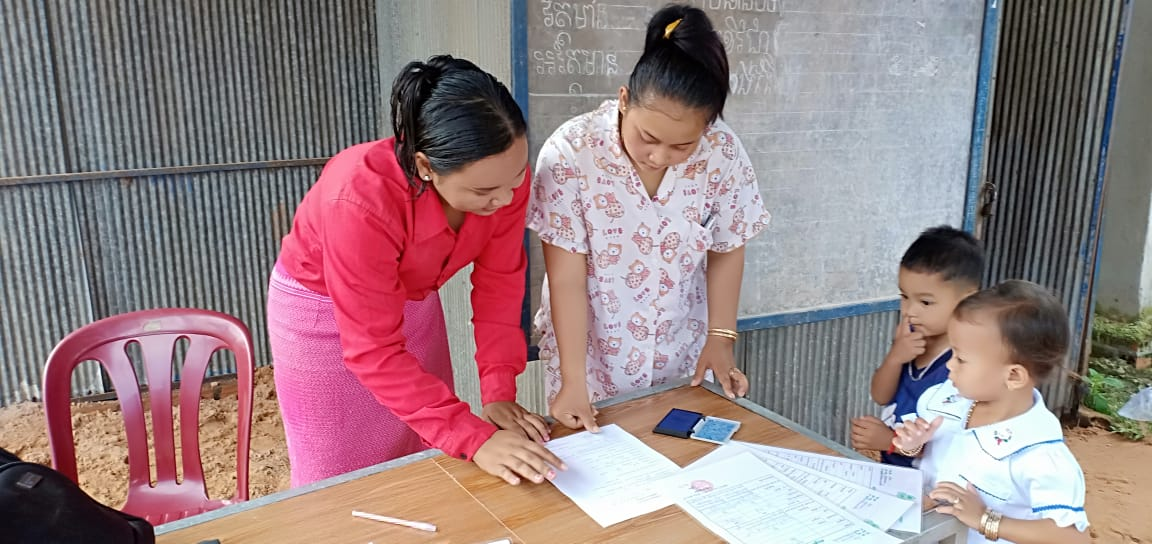 Photo: In Paurn Village, Banteay Meas District, Kampot Province, a mother (photo right) agrees to enroll her child to join the Village Based Preschool by thumbprinting on student's enrollment form.