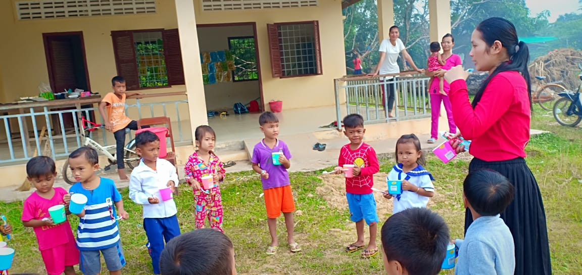 Photo: Preythom Village Based Preschool Teacher Srey May instructs students on oral health care.