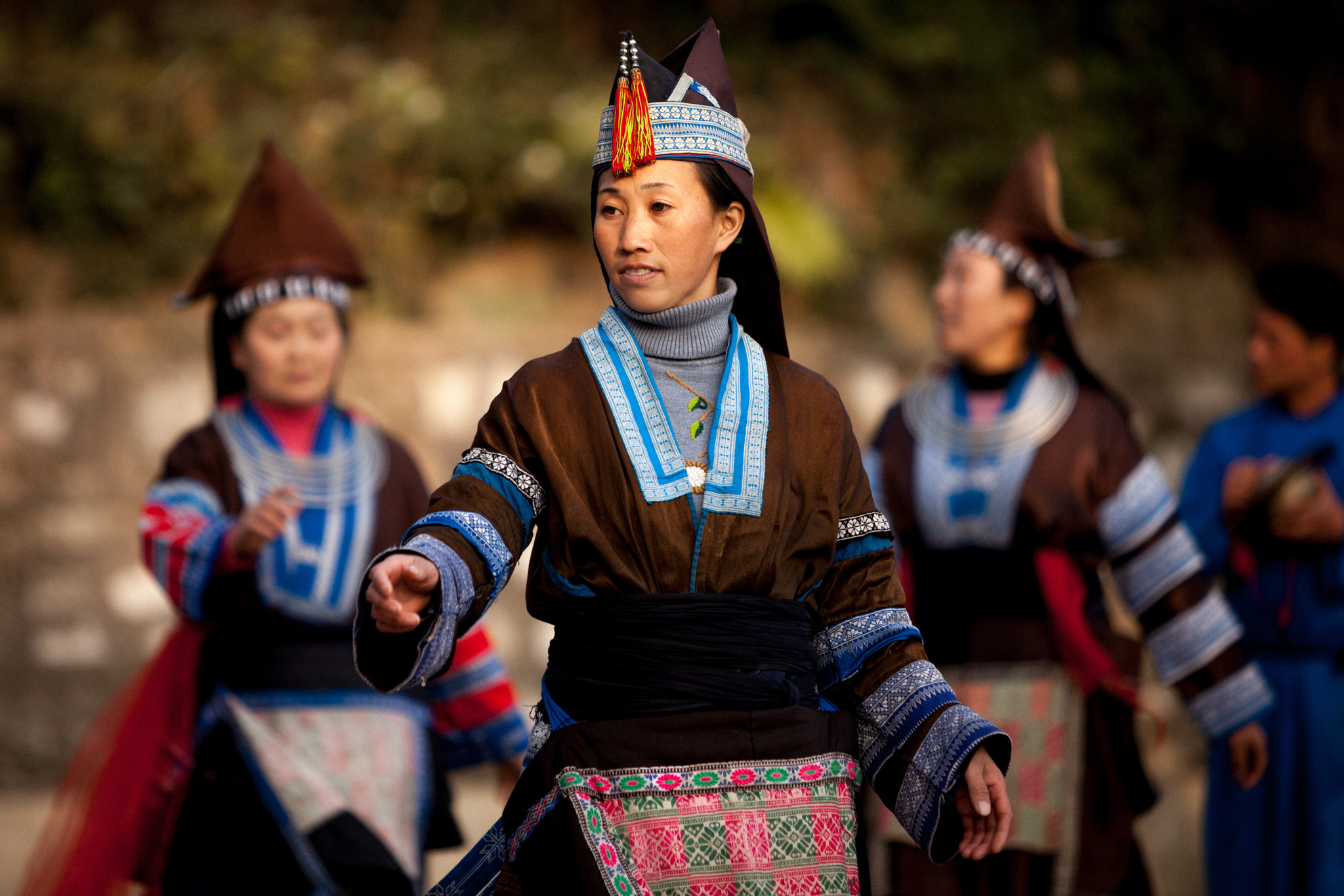 Miao women performing a traditional folk dance to welcome travellers to the village.