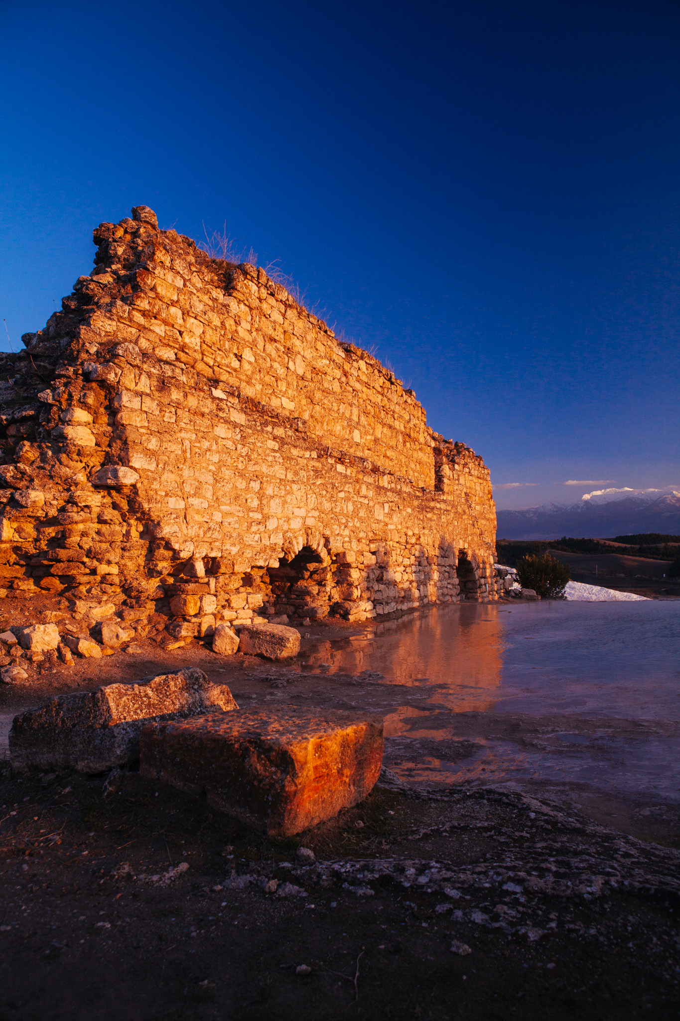 An ancient wall glows in the sunset at Pamukkale . Denizli Turkey