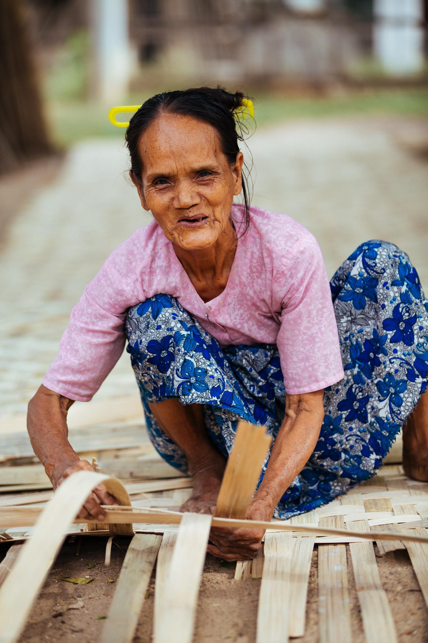 A local village woman weaving going about her mat weaving.