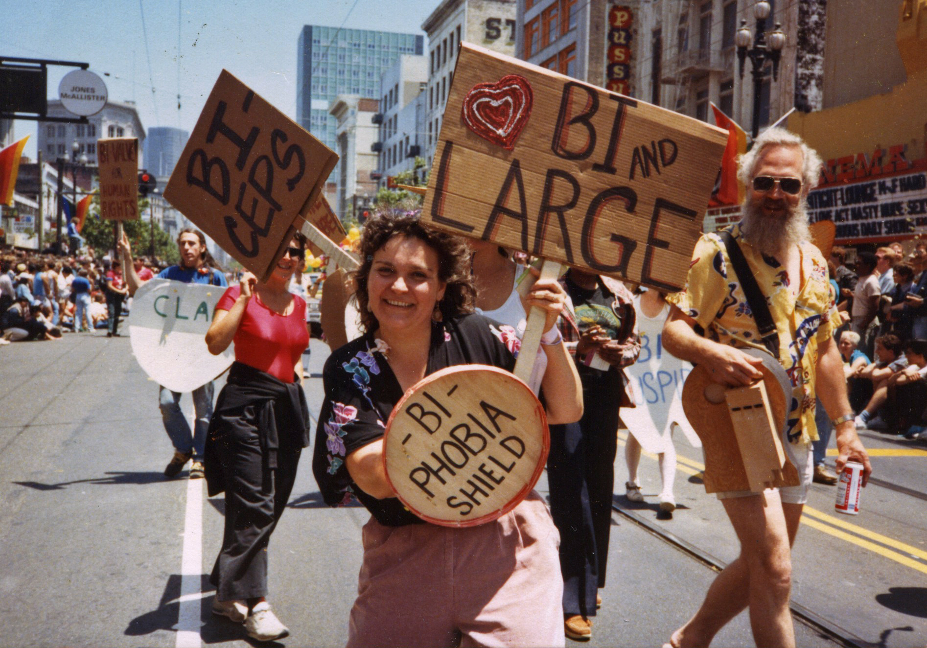"""Arlene Krantz, BiPOL co-founder Lani Ka'ahumanu wields her """"Bi-Phobia Shield"""" as she marches with her contingent in the 1984 Lesbian and Gay Freedom Day Parade (1984). Left to right: BiPOL co-founder Bill Mack, Lynne Frawley, Ka'ahumanu, unknown."""