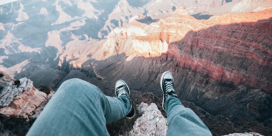 adveturer-legs-dangle-over-canyon-edge_925xcrop.jpg