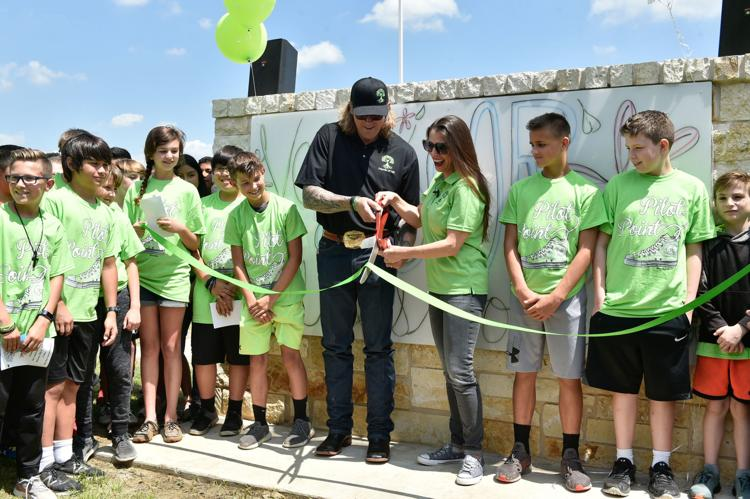 Chad Chance and Susan Chance are surrounded by students as they cut a ribbon during a dedication ceremony for Vail's Outdoor Classroom on Wednesday at Pilot Point Intermediate School.