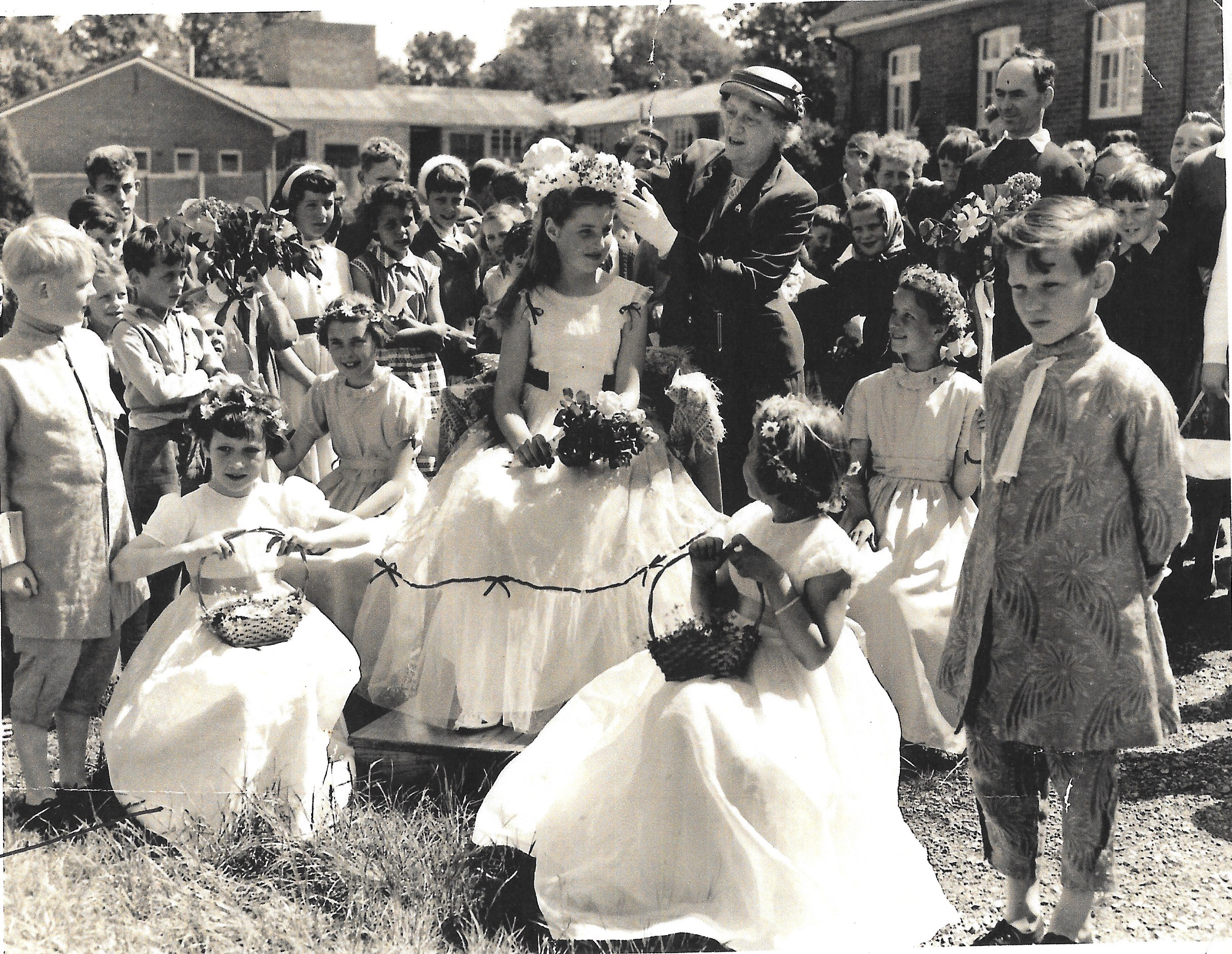 "This picture appeared in the newspaper in 1956(?) with the headline ""Stanmore's pretty May Queen""  The caption read: ""The Mayor of Winchester, Councillor Miss E. M. Barnes, crowns the May Queen after opening Stanmore Fete. The pretty May Queen is Miss Penelope Hudd and her attendants are Ann Mason, Angela Martin, Amanda Trigg and Glenis Sommerbell; and the two pages, Anthony Stride and Richard Bramley."