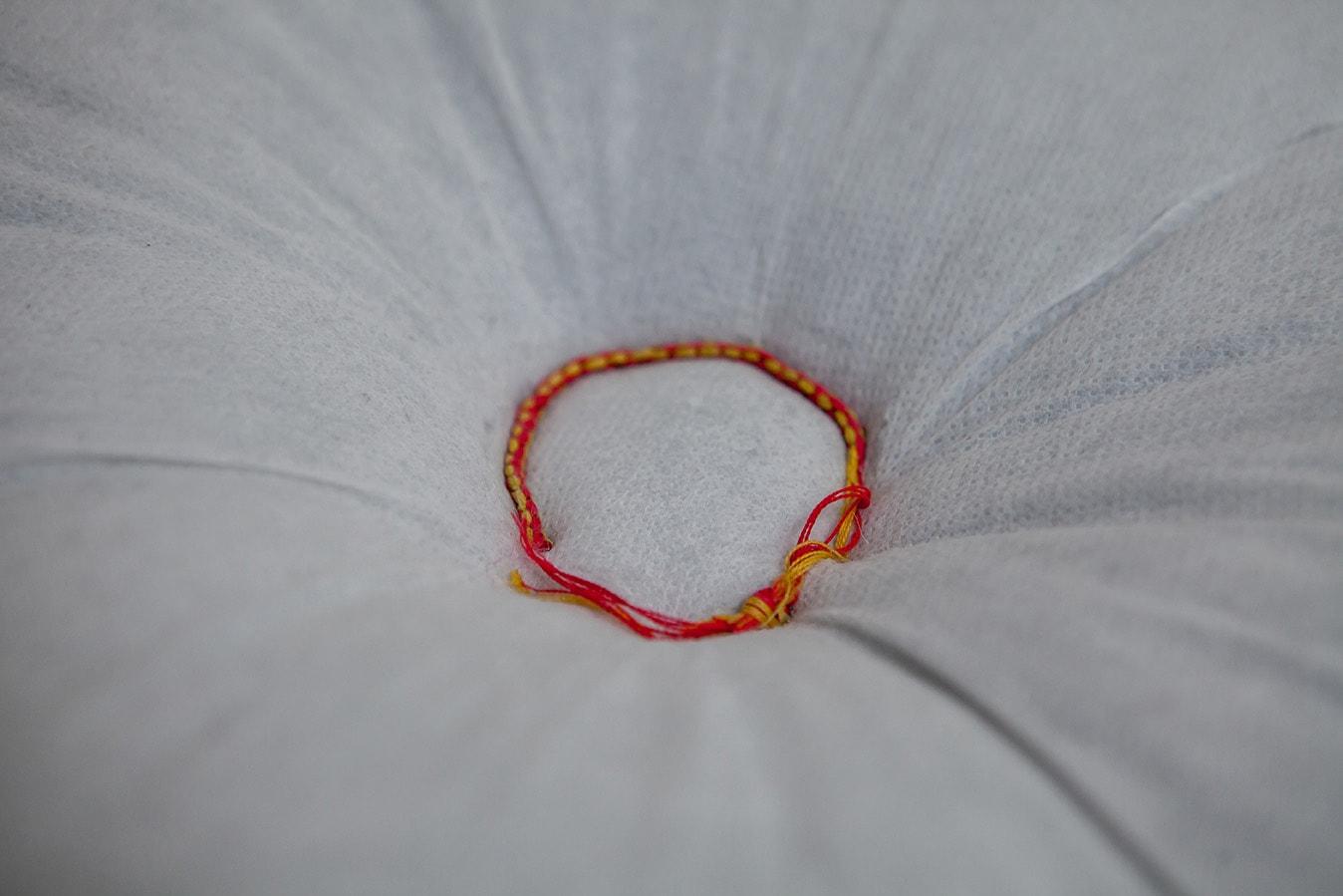 Le poids d'un vœu, (H x L x l): 5 cm x 20 cm x 20 cm Coussin, bracelet bouddhiste 2016