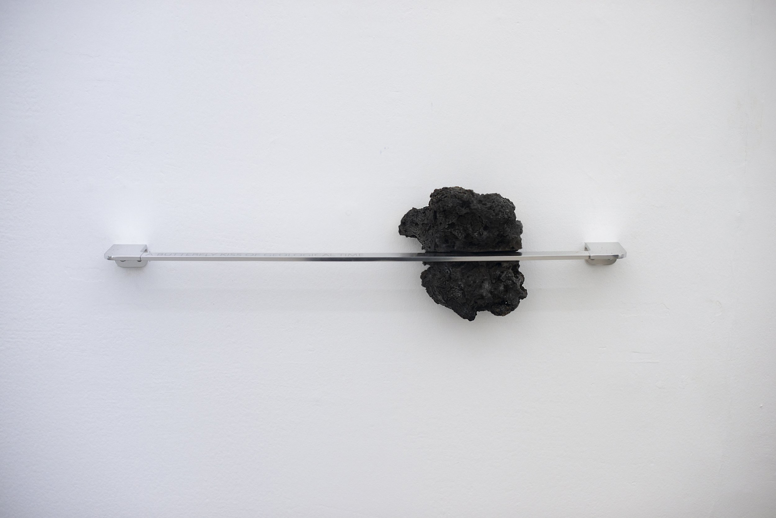 PLASTICITY -  A butterfly kiss of geological time.  Volcanic stones, Steel chains, Orthopedic pillow, Engraved aluminum, Towel rack. Variable dimensions