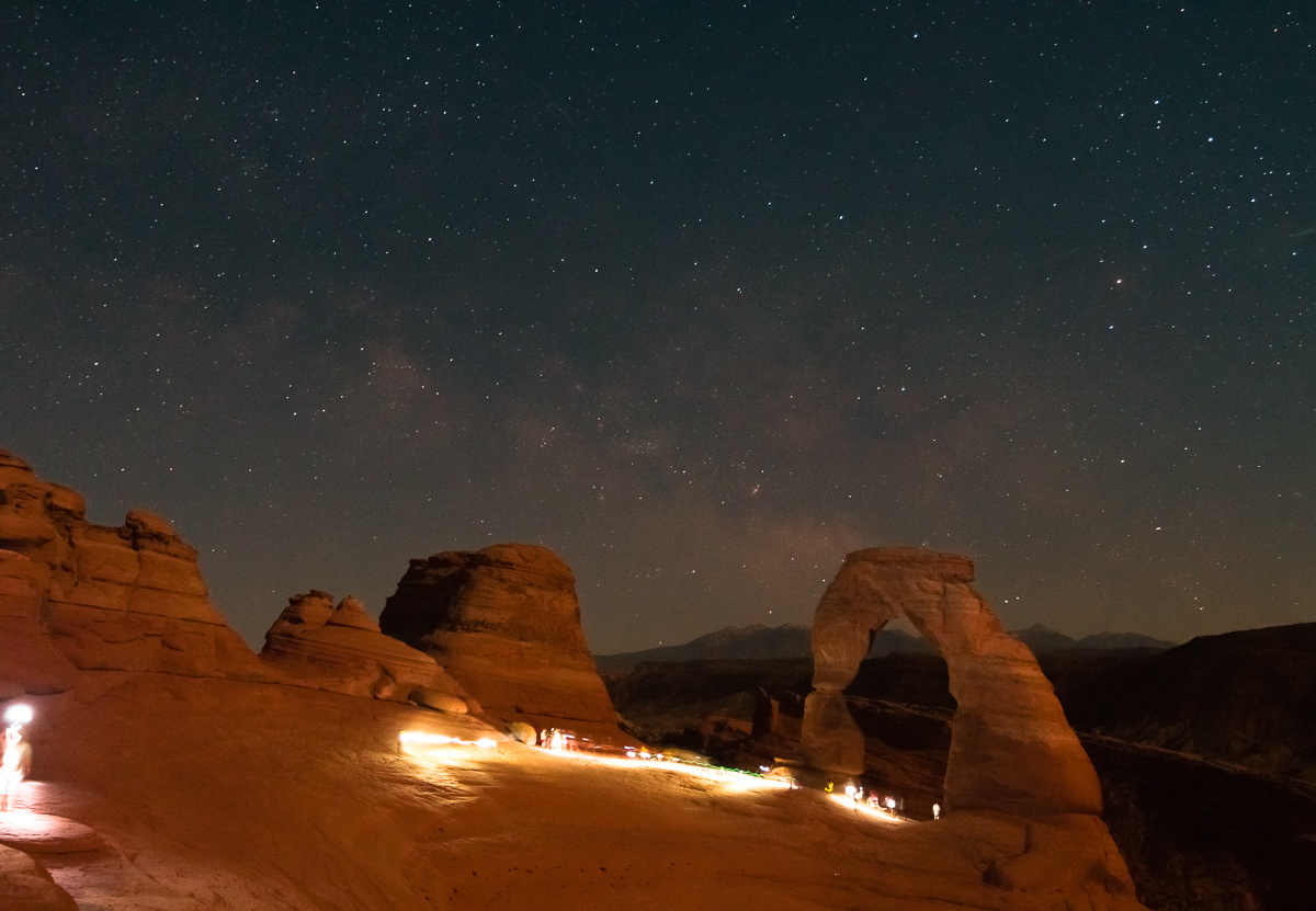 Hikers Illuminate Delicate Arch as the Milky Way rises