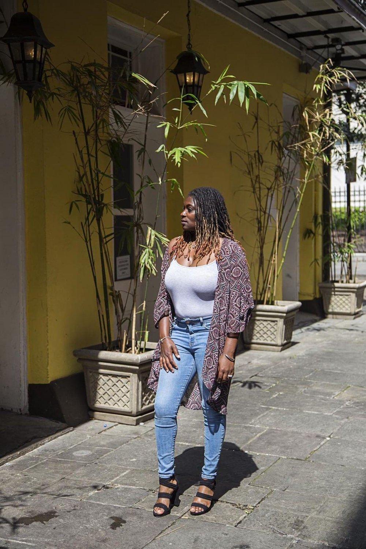 Black woman wear jeans and purple kimono top.