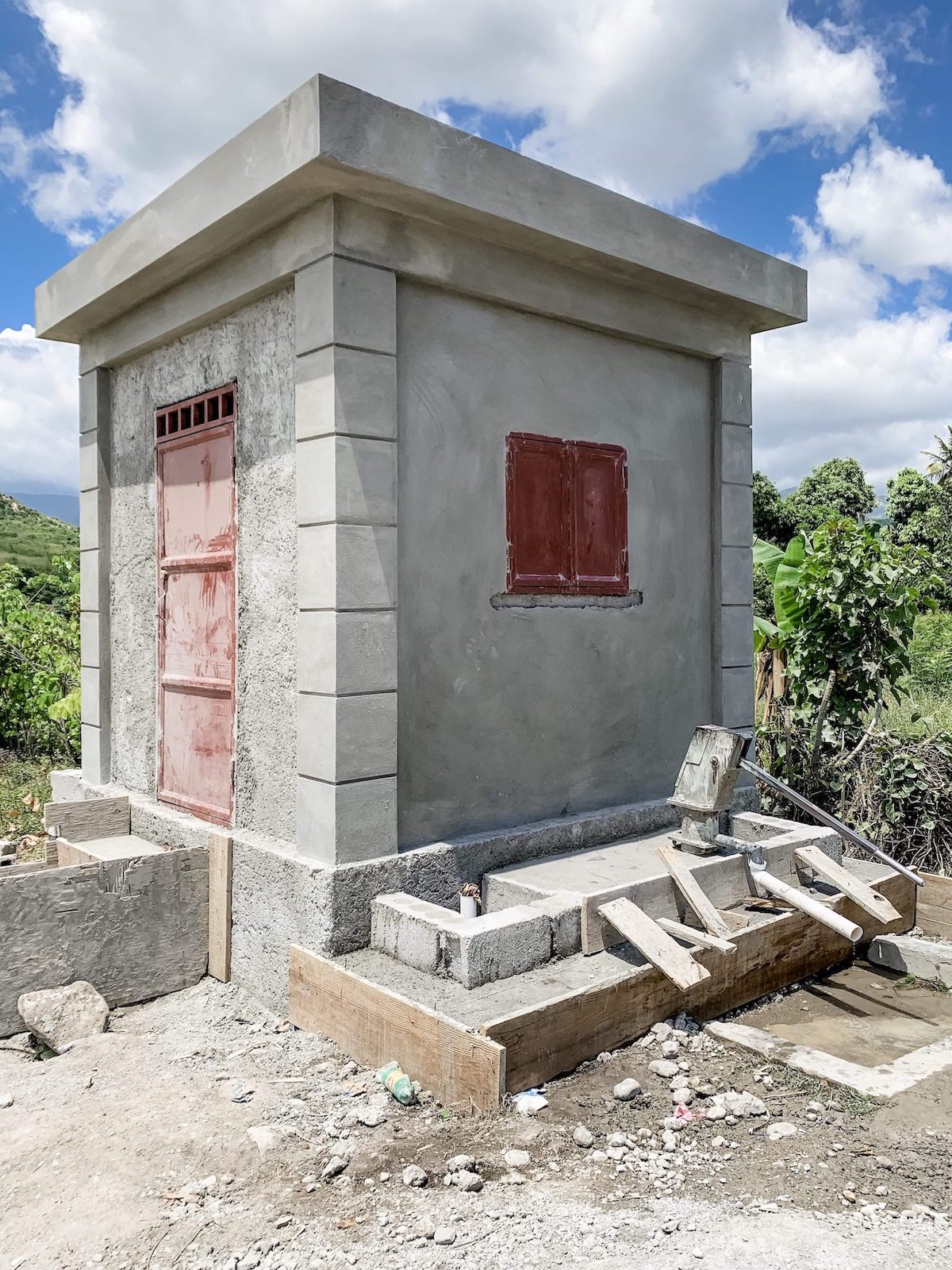 THE WATER WELL IN LA BEYI! YOU CAN SEE A HAND PUMP WELL AT THE FRONT OF THE BUILDING, WHICH THEY DESCRIBED CAN BE USED FOR CLEANING PURPOSES. INSIDE, THERE WILL BE A MORE SOPHISTICATED SYSTEM THAT WILL FILTER AND CHLORINATE WATER FOR DRINKING!  WATCH THIS VIDEO TO SEE HOW IT WILL WORK!
