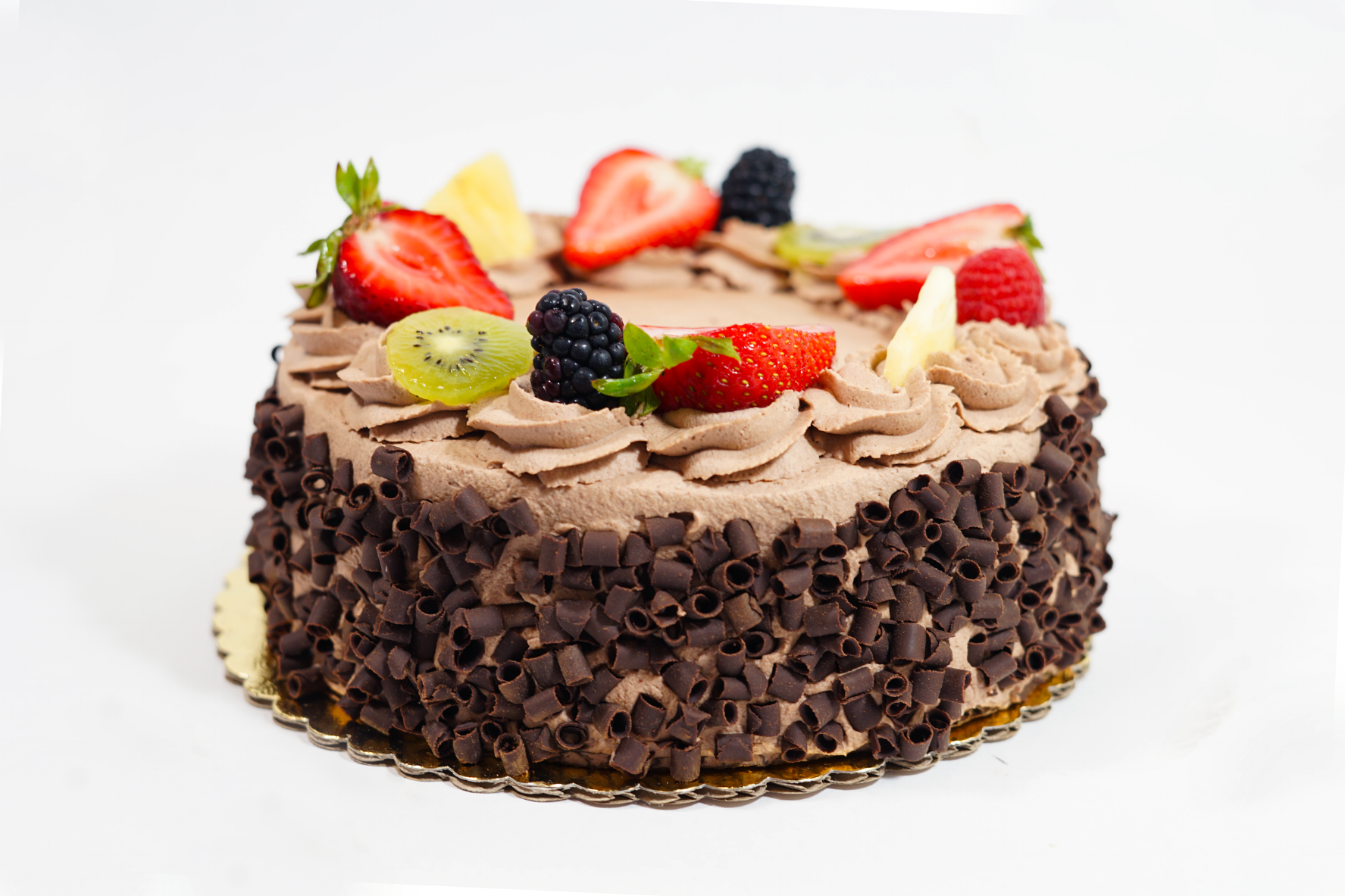 Chocolate Nicois - A chocolate cake with raspberry syrup, chocolate Bavarian cream, raspberry coulis, fresh seasonal fruit filling, and a layer of apricot preserve filling. Iced with chocolate whipped cream and sides covered with chocolate curls.