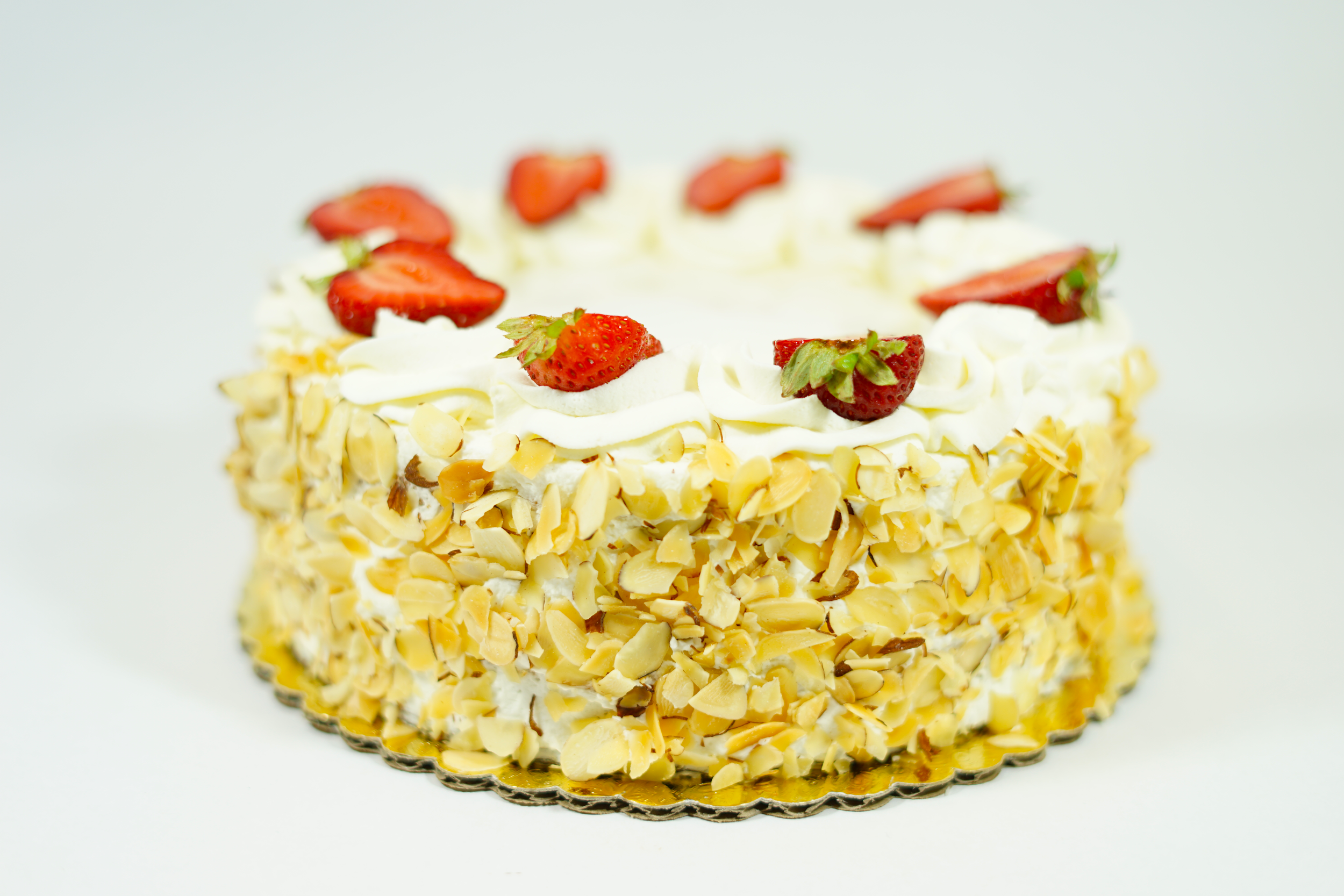 Strawberry Shortcake - A white cake with raspberry syrup, Bavarian cream, layer of strawberry preserve, fresh strawberries, and raspberry coulis filling. Iced with whipped cream and sides covered with slivers of almonds.