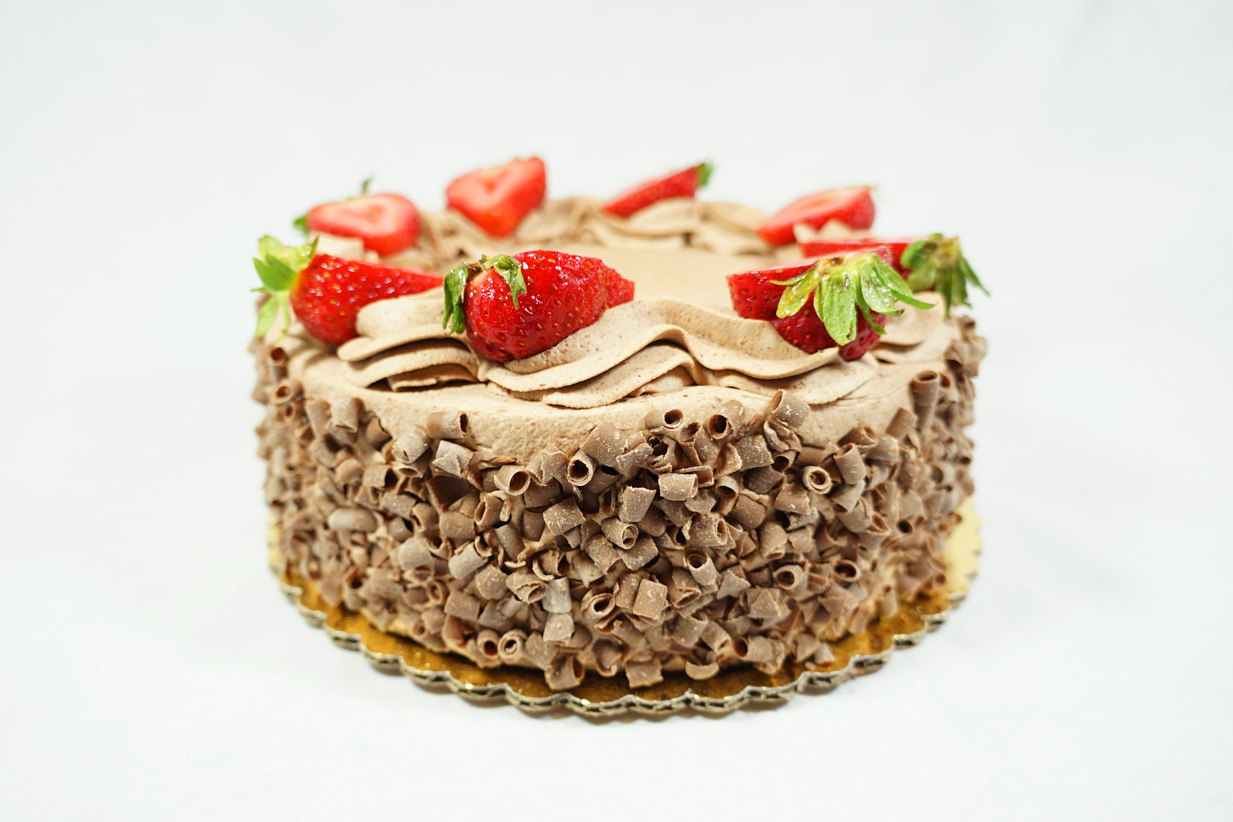 Chocolate S.S.C - A chocolate cake with raspberry syrup, chocolate Bavarian cream, a layer of raspberry coulis, fresh cut strawberries and strawberry preserve filling. Iced with chocolate whipped cream and sides covered with chocolate curls.