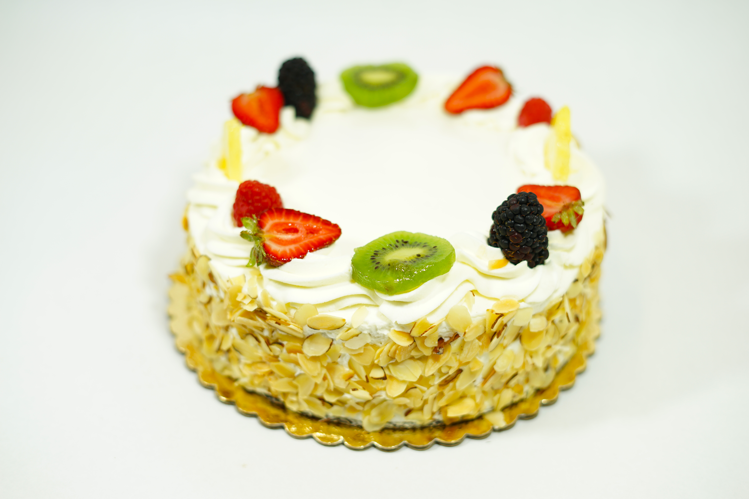 Nicois - A white cake with raspberry syrup, a layer of apricot preserve, Bavarian cream with raspberry coulis and fresh seasonal fruits. Iced with whip cream, sugar fondant and toasted slivered almonds on the sides.