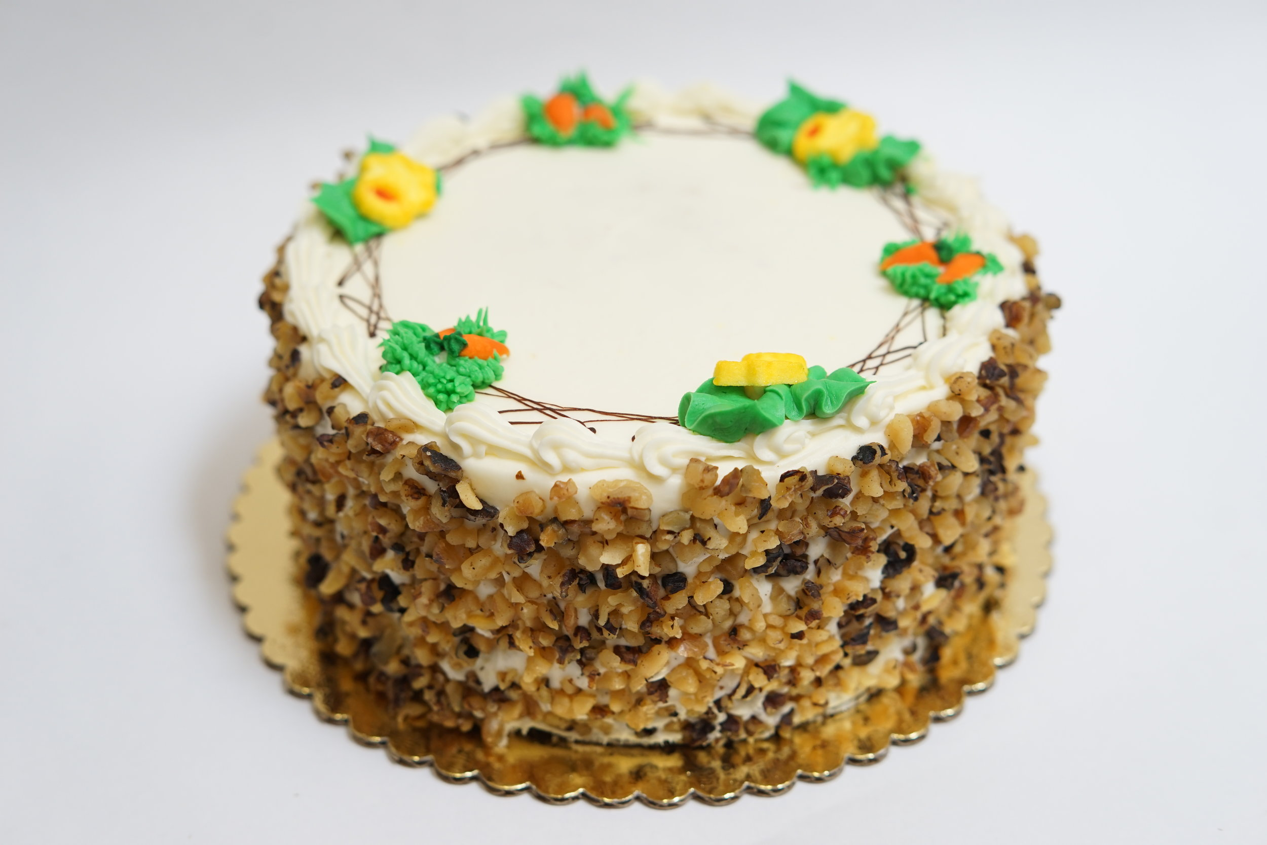 Carrot - A cake made with an organic, grated carrot, pecan and raisin mix. Filled with cream cheese icing and sides covered with walnuts.