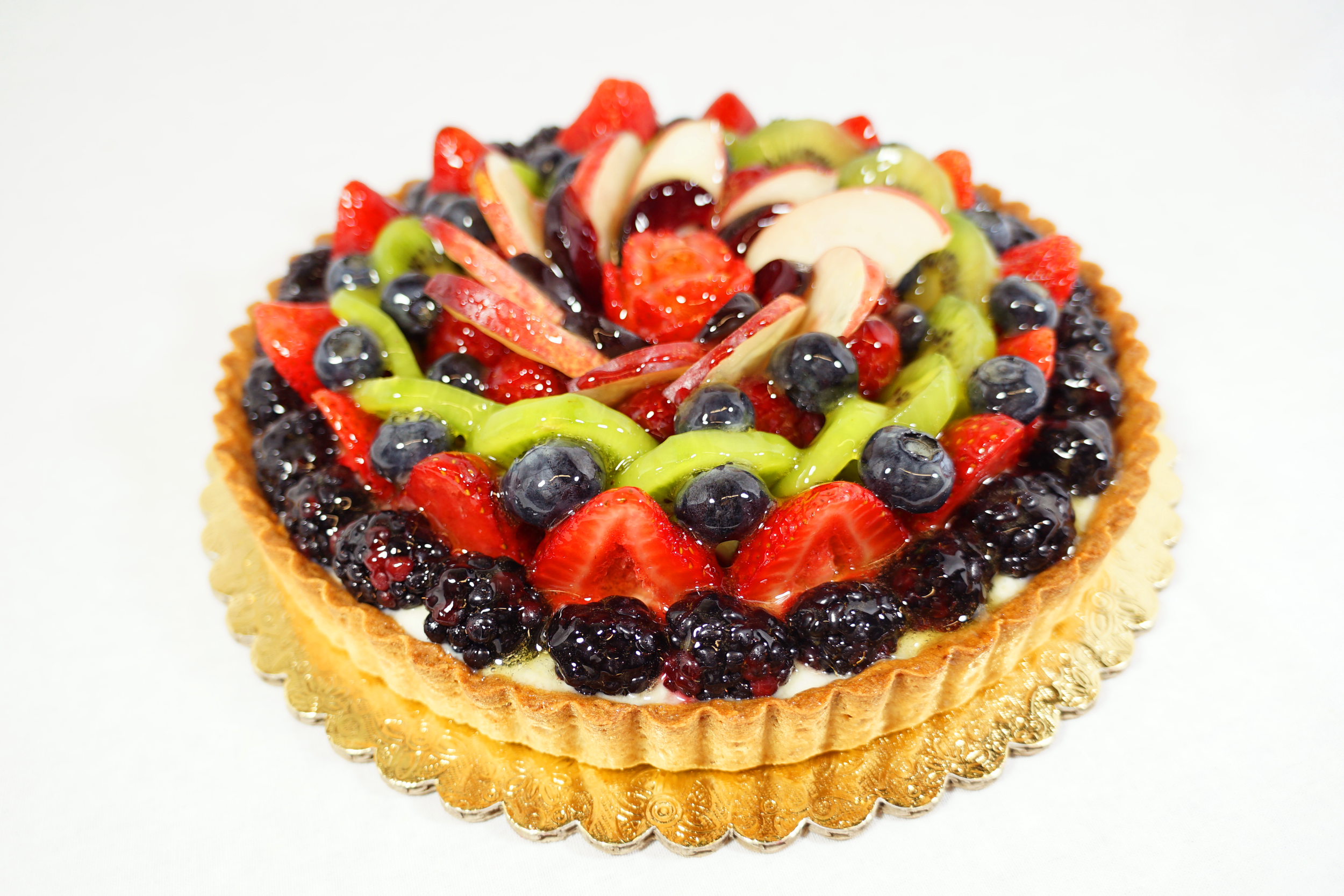 Mixed Fruit - An almond pastry shell filled with mascarpone cream and raspberry coulis. Topped with assorted fruit on a marzipan strip.