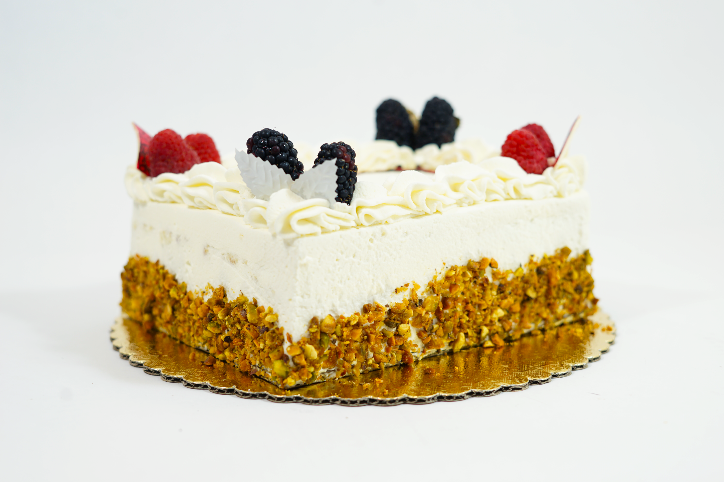 Passion Fruit - Sponge cake with raspberry syrup preserve and passion fruit creme madame filling. Iced with whipped cream and sides covered with roasted unsalted pistachio.