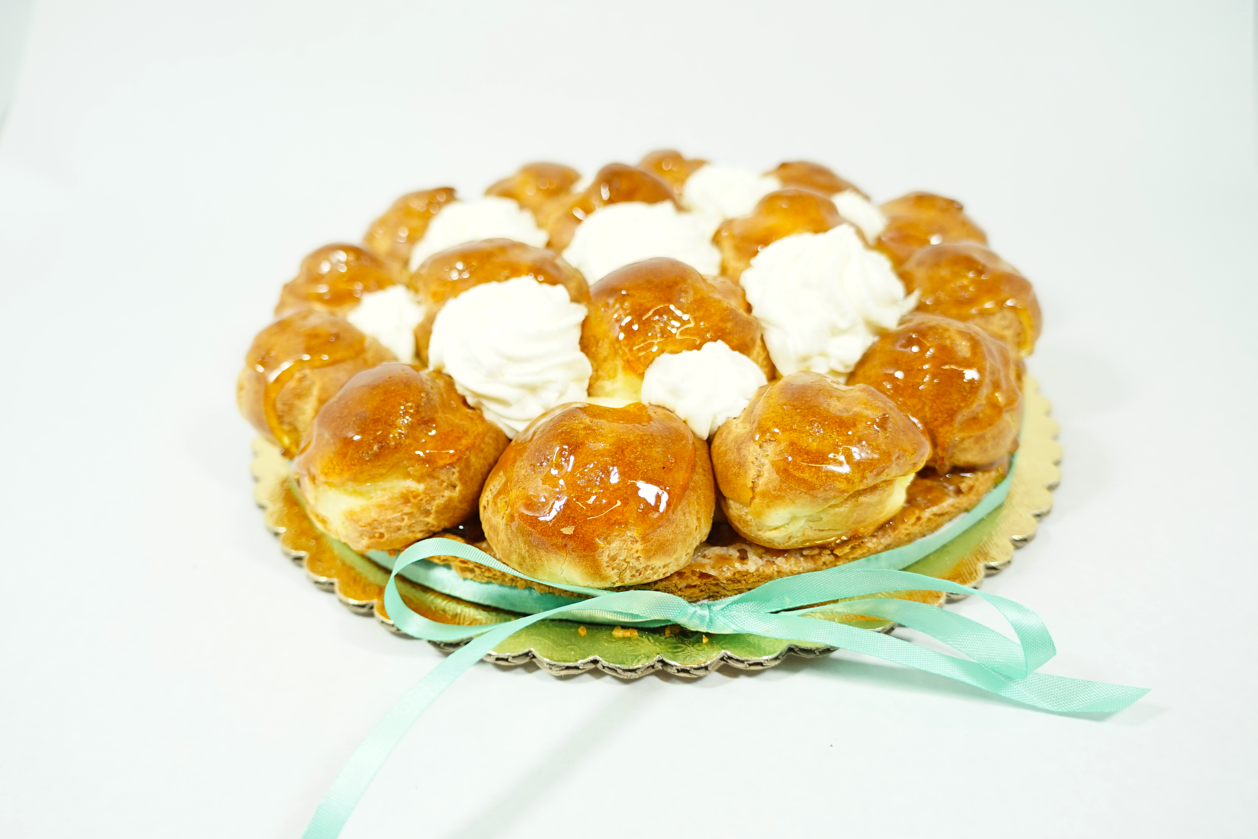 St. Honorae - A unique, traditional french cake made with cream filled puff pastry ball laid in a circle form. Topped with Bavarian cream decorated with caramel choux.