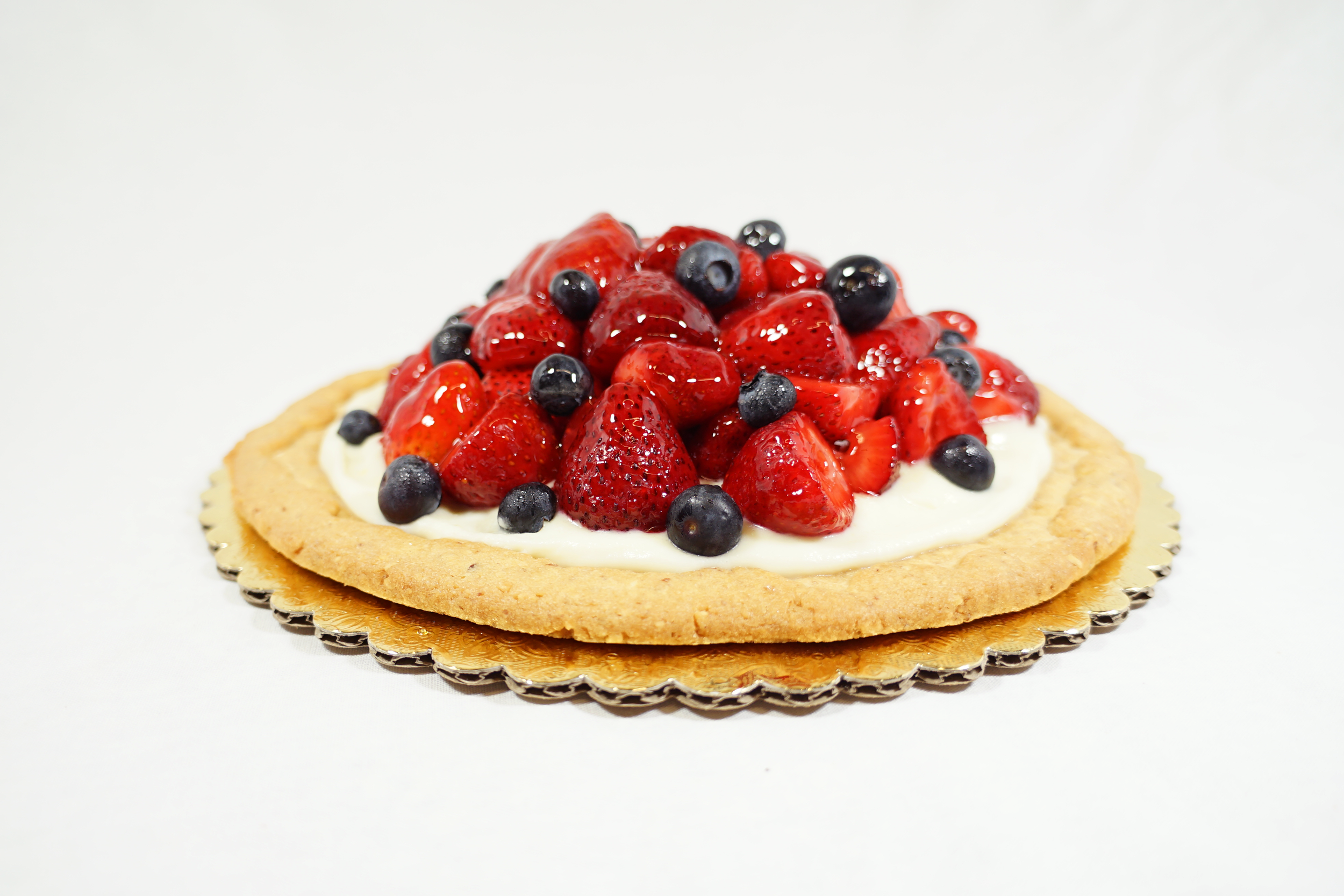 Strawberry Pizza - A sweet almond tart shell with sweetened mascarpone filling. Topped with a mix of fresh sliced strawberries, blueberries and strawberry puree.