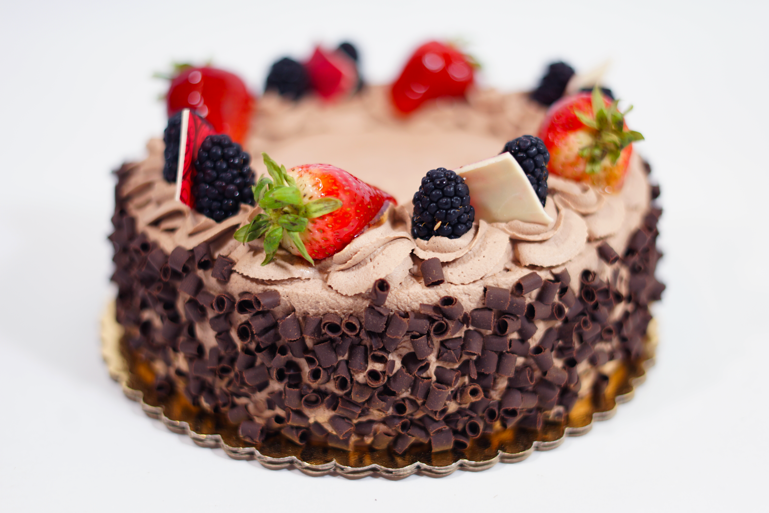 Marquis - Chocolate cake with raspberry syrup, chocolate Bavarian cream, and a layer of apricot preserve filling. Iced with chocolate whipped cream and sides covered with chocolate curls.