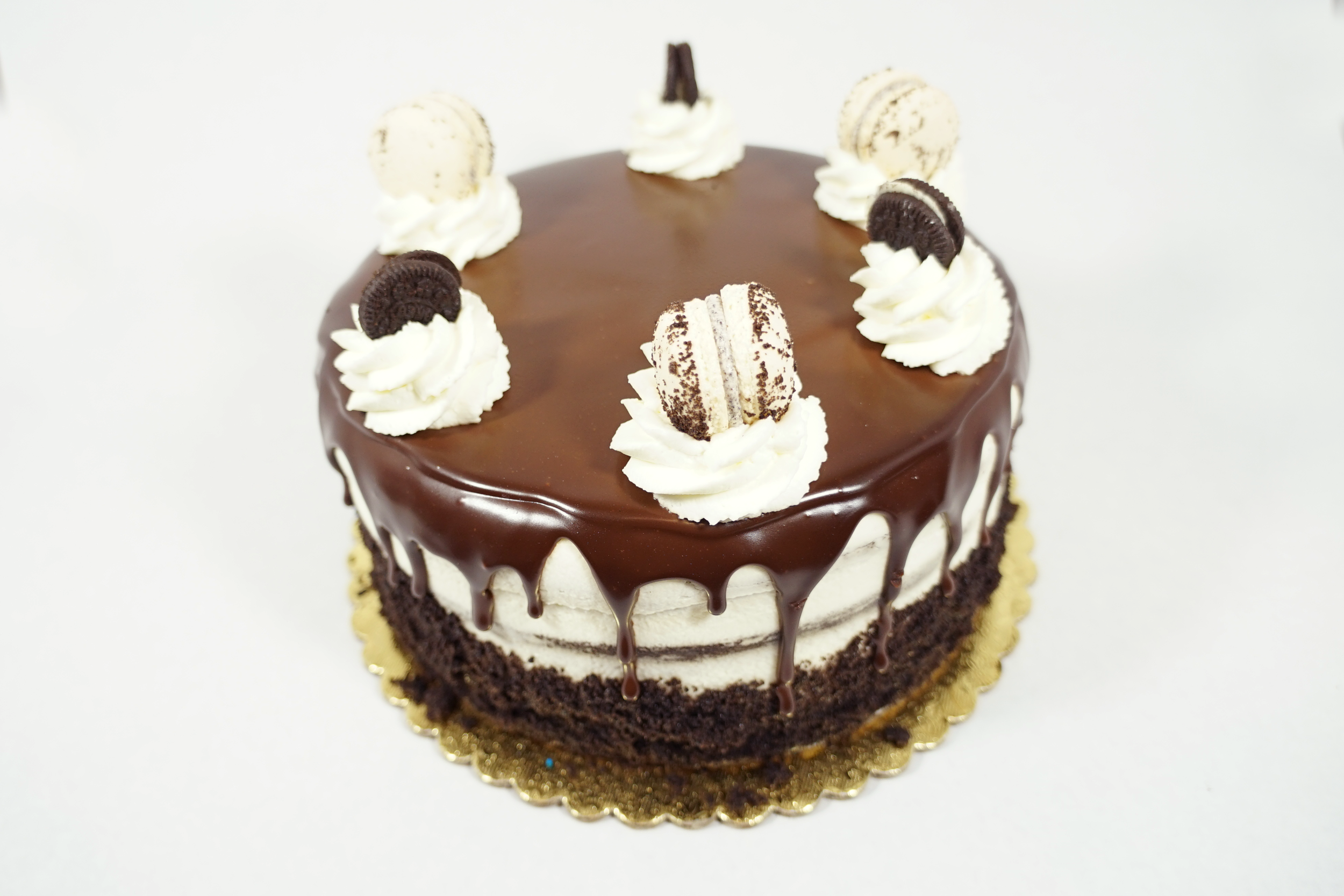 Cookies and Cream - Chocolate cake with rum syrup and 2 layers of Oreo cream filling. Iced with whipped cream. Poured on top a layer of melted chocolate glaze drip. Decorated with crumbled chocolate cookie, dallops of whipped cream and mini Oreos.